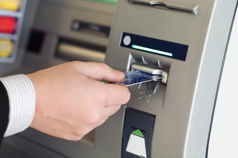 Den manliga handaffärsmannen sätter in kreditkorten in i ATMEN royaltyfria bilder