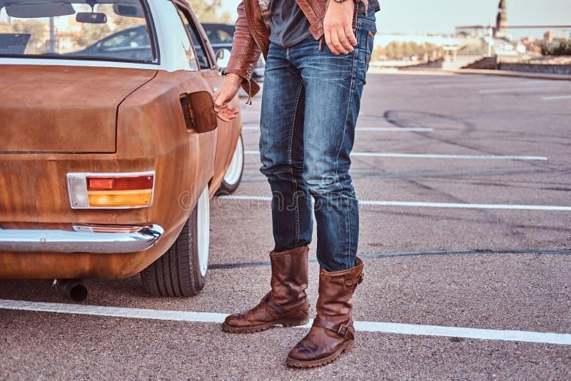Den manliga handen öppnar gaslocket av en stämd retro bil för att tanka fotografering för bildbyråer