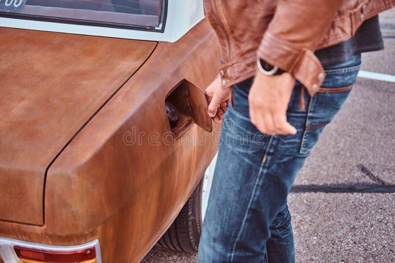 Den manliga handen öppnar gaslocket av en stämd retro bil för att tanka arkivfoto