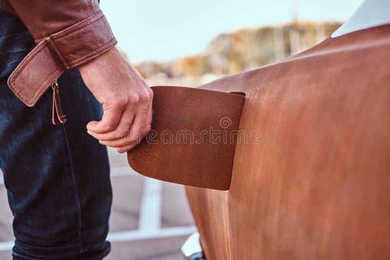 Den manliga handen öppnar gaslocket av en stämd retro bil för att tanka royaltyfri fotografi