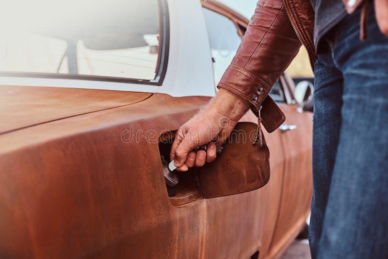 Den manliga handen öppnar gaslocket av en stämd retro bil för att tanka royaltyfri foto