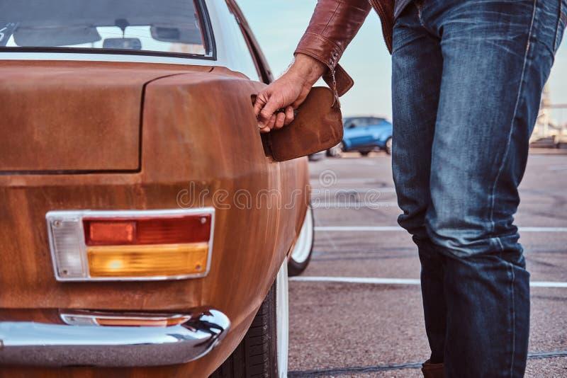 Den manliga handen öppnar gaslocket av en stämd retro bil för att tanka royaltyfria bilder