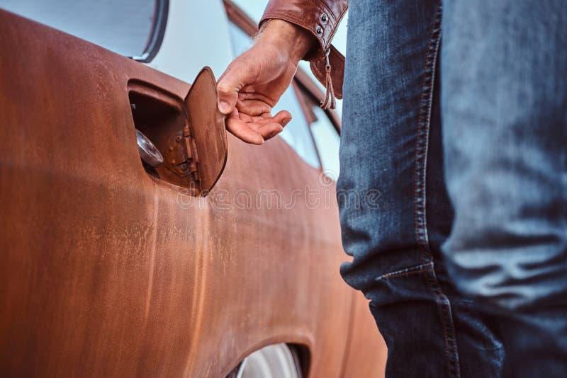 Den manliga handen öppnar gaslocket av en stämd retro bil för att tanka arkivfoton
