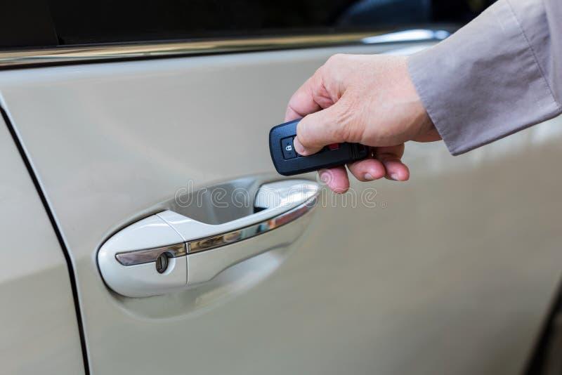Den manliga handen öppnar den vita bilen med keyless tillträdesfunktion arkivbild