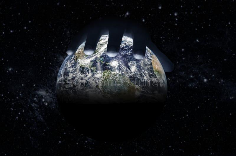 Den manliga handen ligger ?verst av jordklotet mot den stj?rnklara himlen arkivbilder