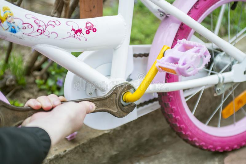 Den manliga handen med en skiftnyckel reparerar ett barns cykel Tj?nste- cykel Cykelreparation arkivbilder