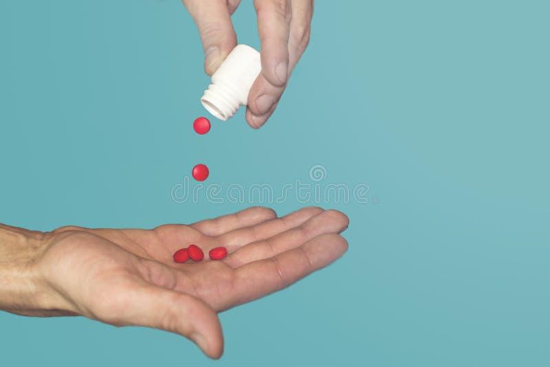 Den manliga handen med piller, röda piller hälls ut ur ett rör arkivbilder
