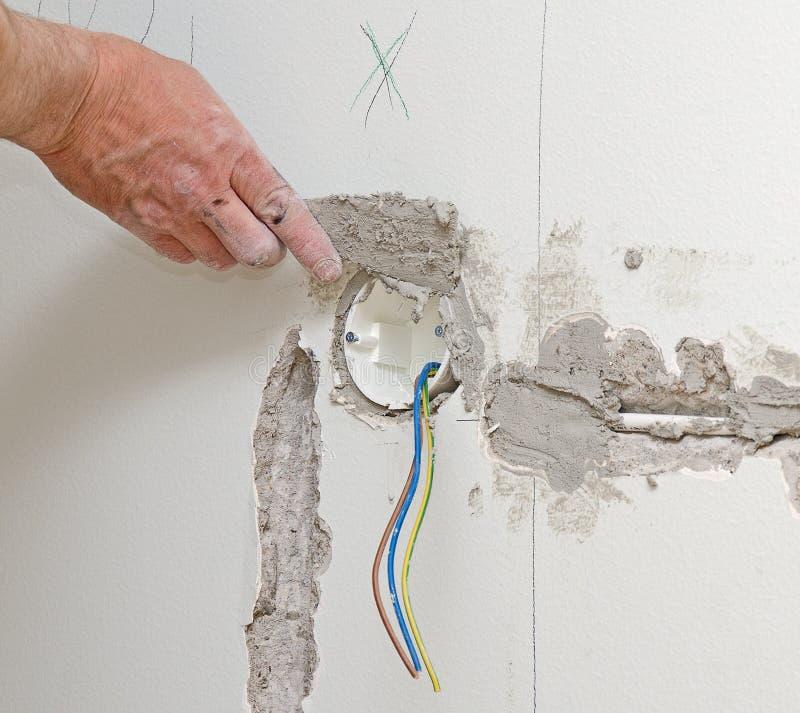 Den manliga handen reparerar väggen arkivbilder