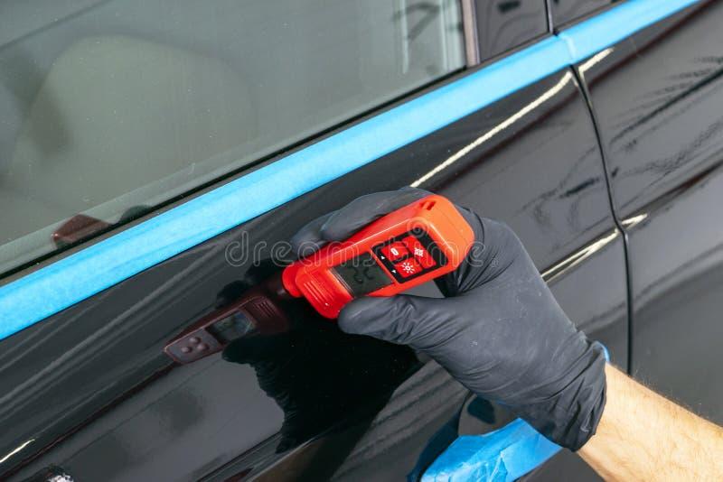 Den manliga handen rymmer apparaten för att mäta beläggningstjocklek, innan den polerar bilen Mäta tjocklek av bilmålarfärgbelägg arkivfoton