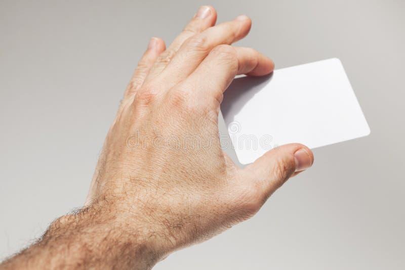Den manliga handen rymmer det vita tomma kortet på den gråa väggen arkivbilder