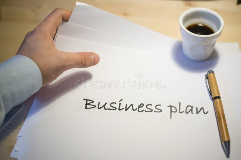 Den manliga handen som pekar på ett affärsplan, skrivev ut på ett vitt ark av papper under ett affärsmöte royaltyfri bild