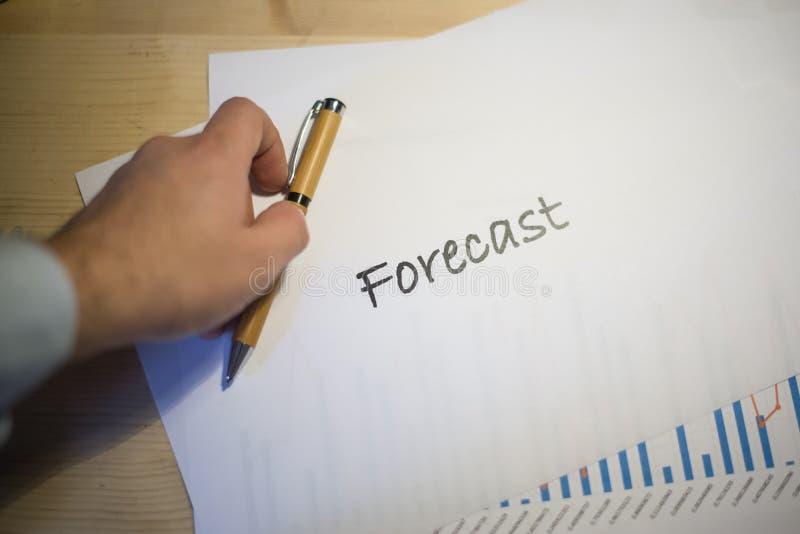Den manliga handen som pekar på ett prognosdokument, skrivev ut på ett vitt ark av papper under ett affärsmöte arkivbilder