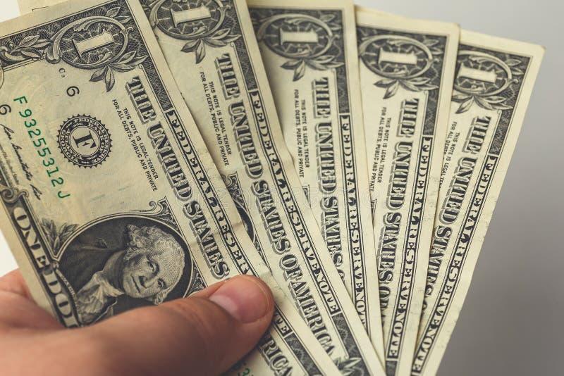 Den manliga handen som rymmer flera en dollar räkningar, pengar är åtsittande, armod och konkursbegreppet arkivbild