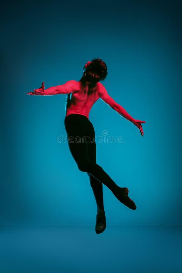 Den manliga idrotts- balettdansören som utför dans på blå bakgrund härlig för studiokvinna för par dans skjutit barn Balettbegrep arkivfoton