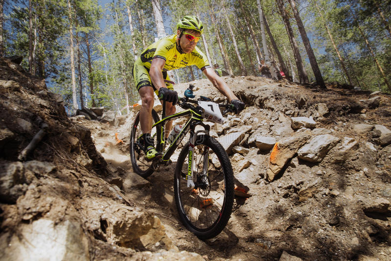 den manliga idrottsman nencyklisten rider ner berget på stenar royaltyfria bilder