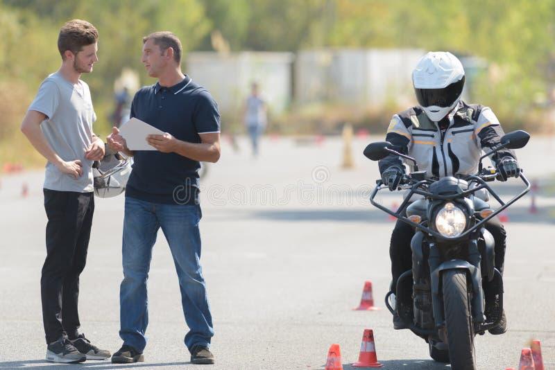 Den manliga instruktören kontrollerar chauffören arkivfoton