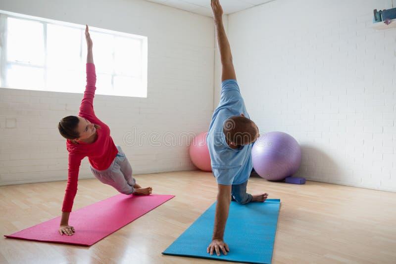 Den manliga instruktören med den praktiserande sidoplankan för studenten poserar i yogastudio royaltyfri bild