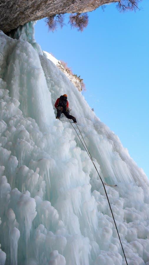 Den manliga isklättraren på den sista graden av en mycket hård och brant isnedgång i ett smalt vaggar gullyen i fjällängarna arkivfoto