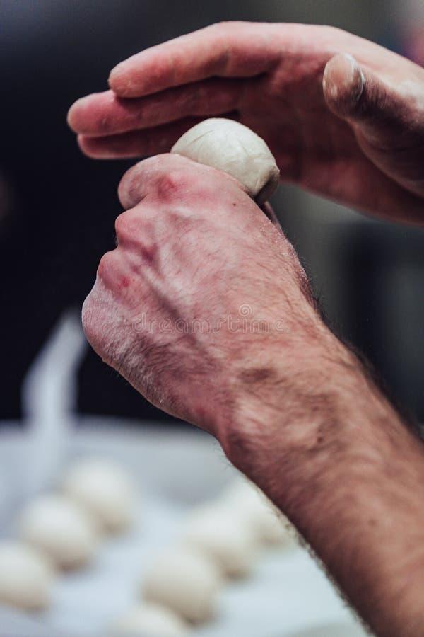 Den manliga kocken Preparing Bread Dough för själv gjorde bröd och små pastejer - kökuppsättning med handling, endast kockens hän arkivbilder