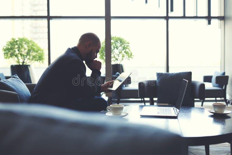 Den manliga kompetenta krubban är läs- nyheterna på websiten via den digitala minnestavlan, medan sitter i kafé fotografering för bildbyråer
