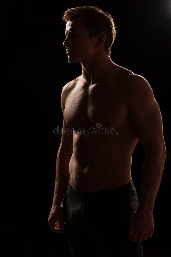 Den manliga konditionmodellvisningen tränga sig in i studio arkivfoton