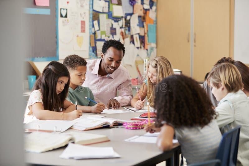 Den manliga läraren arbetar med grundskolaungar på deras skrivbord royaltyfri bild