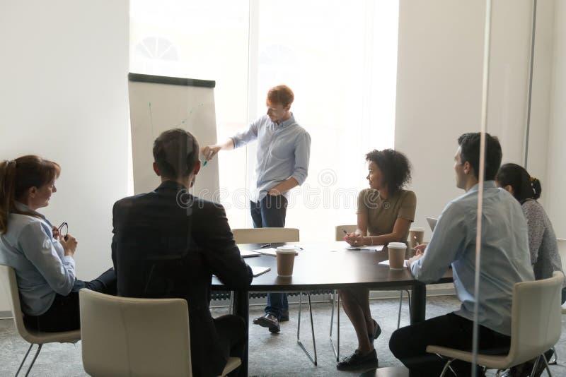 Den manliga lagledaren gör flipchartpresentationen för olika anställda arkivfoto