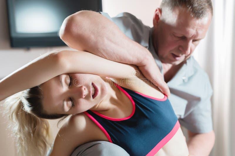 Den manliga manuella inv?rtes terapeutmass?ren behandlar en ung kvinnlig patient Sträckning av ryggen och av det intercostal syst royaltyfri bild