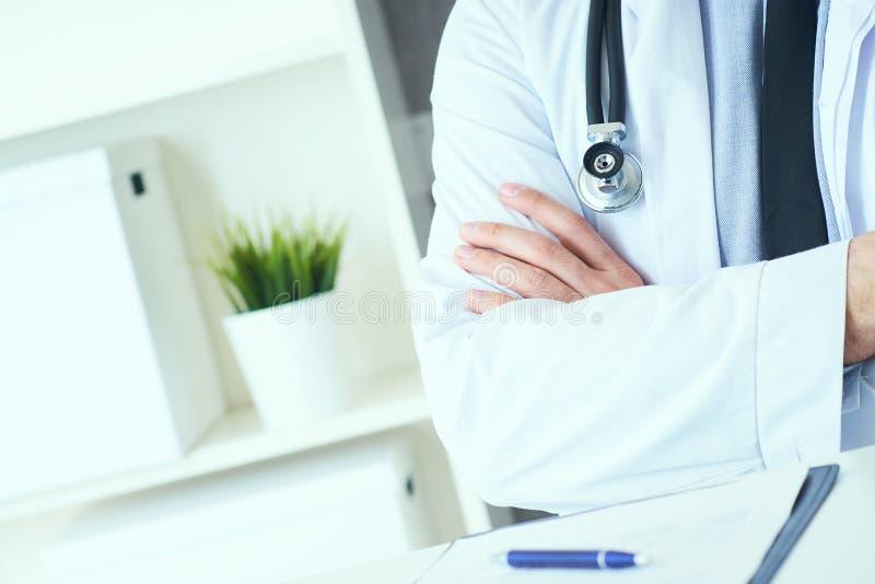 Den manliga medicinska doktorn som poserar med korsade armar, labblaget, stetoskopet och h?nder st?nger sig upp, sjukv?rdprofessi royaltyfri foto