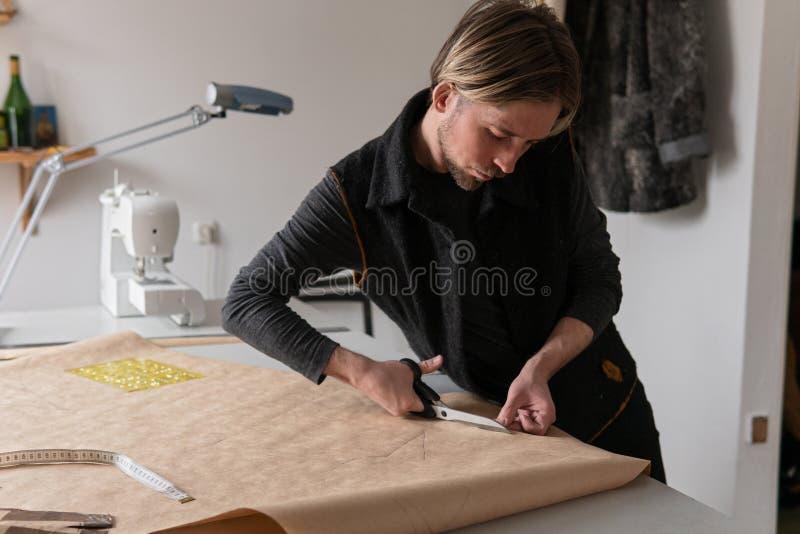 Den manliga modeformgivaren med sax klipper den pappers- bekläda modellen i seminarium royaltyfri bild