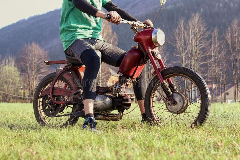 Den manliga modellen sitter p? den veteranmopedJawa 50 banbrytaren R?d renoverad motorcykel av den unga ben?gna pojken Tjeckiskt  royaltyfria foton