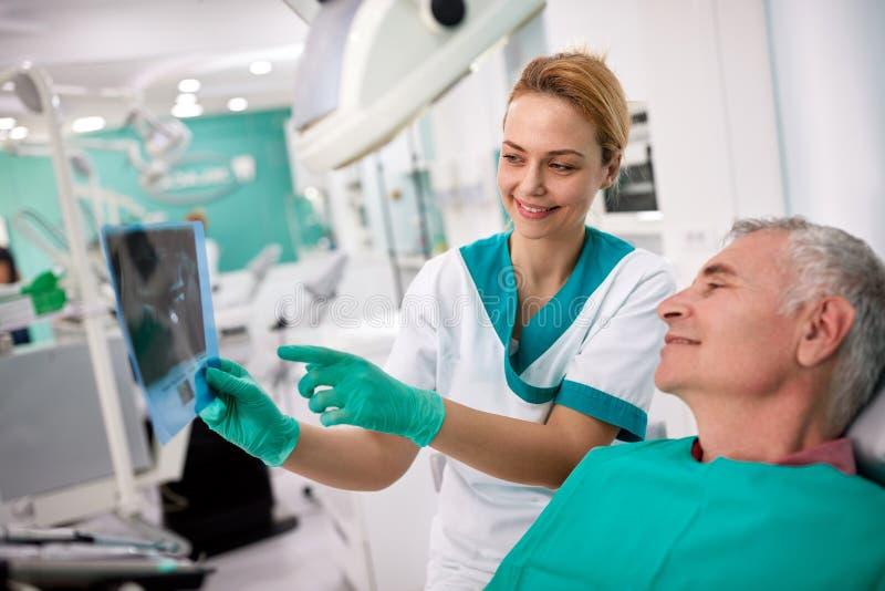 Den manliga patienten och kvinnliga tandläkaren som ser tänder, röntgar arkivbilder