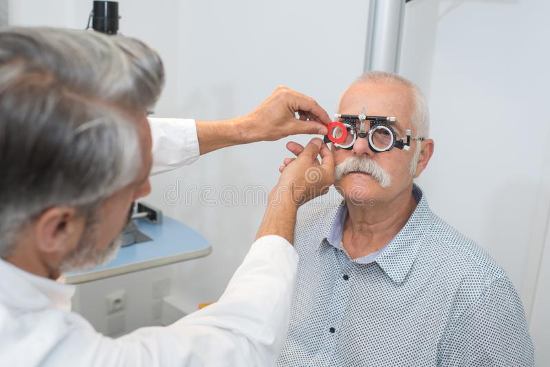 Den manliga pensionären i syncentral undersöker ögon arkivfoton