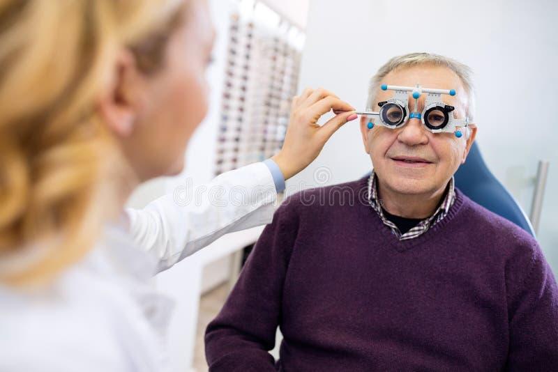 Den manliga pensionären undersöker ögon royaltyfri foto