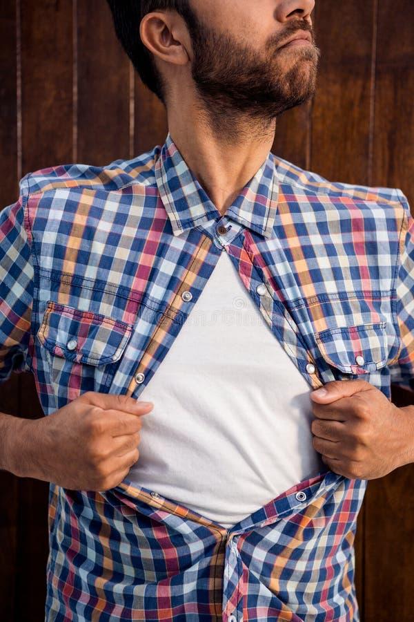 Den manliga professionelln som drar hans skjorta, gillar superheroen royaltyfria bilder