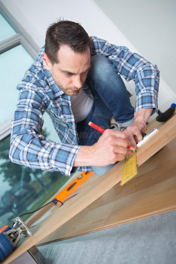 Den manliga snickaren använder att mäta måttband trä royaltyfri bild