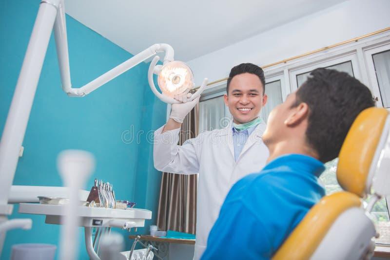 Den manliga tandläkaren justerar strålkastaren, för startande, arbetar royaltyfri bild