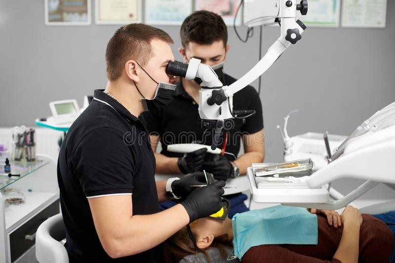Den manliga tandläkaren utför en tand- undersökning med hjälpen av mikroskopet royaltyfri foto