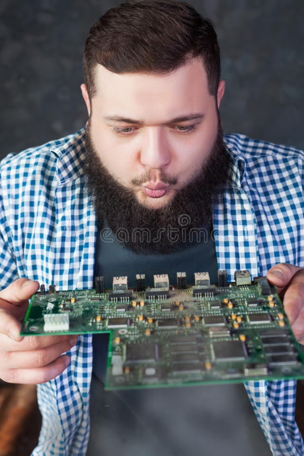 Den manliga teknikern blåser av dammet från moderkortet arkivfoton