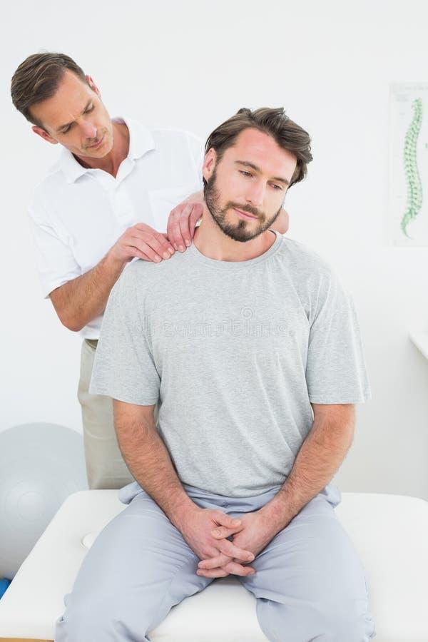Den manliga terapeuten som masserar ett innehåll, mans skuldror fotografering för bildbyråer