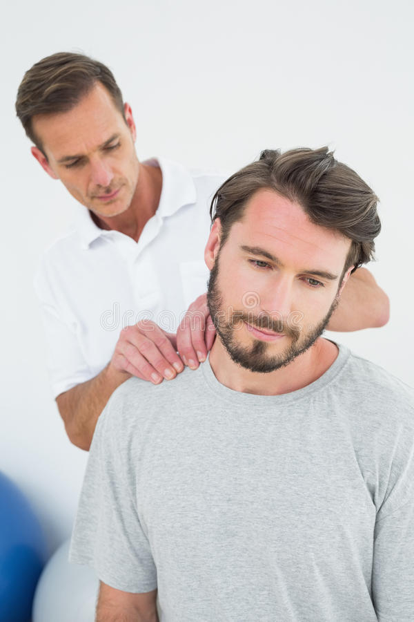 Den manliga terapeuten som masserar ett innehåll, mans skuldror royaltyfri foto