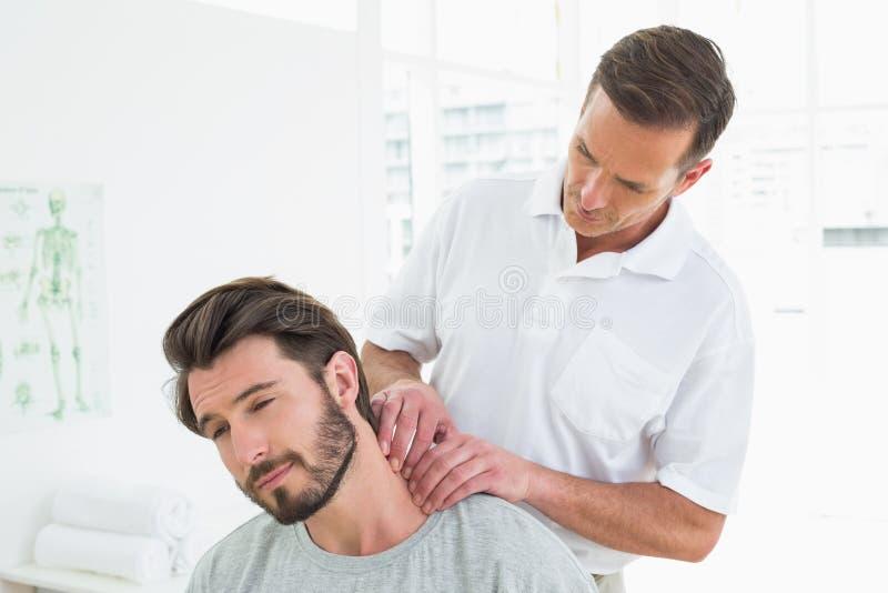 Den manliga terapeuten som masserar ett ungt, mans halsen royaltyfri fotografi