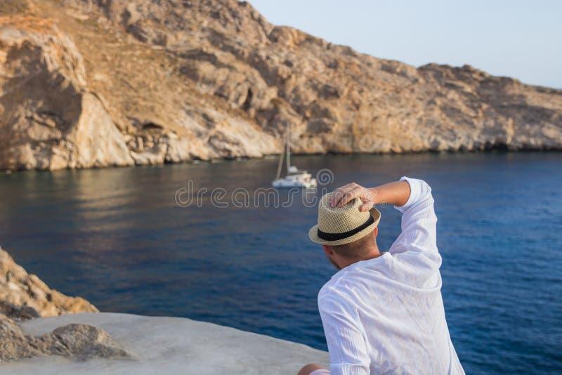 Den manliga tillbaka konturn i hatten tycker om en sikt av den steniga kusten och det blåa havet med en yacht royaltyfri foto
