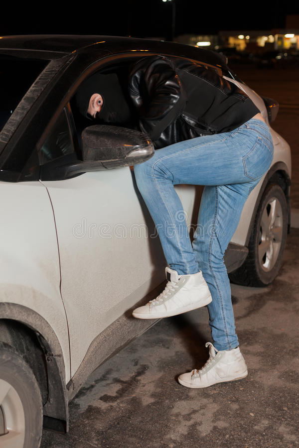 Den manliga tjuven får in i bilen till och med fönstret royaltyfri bild