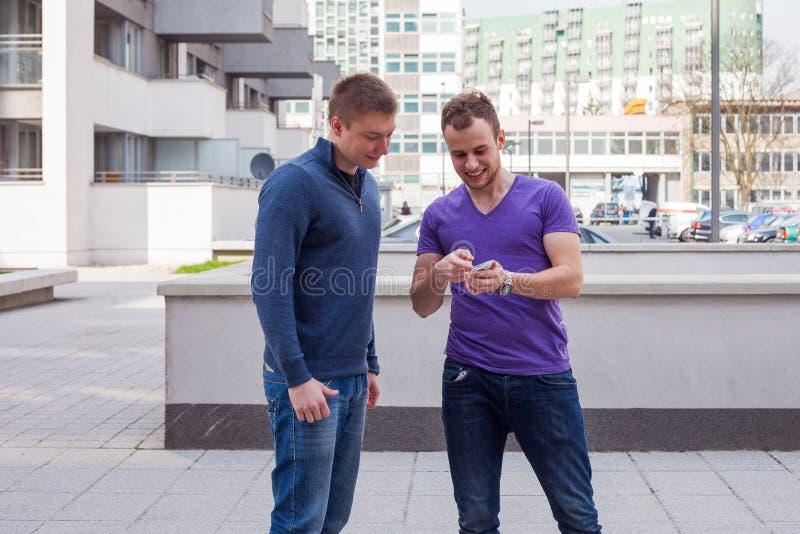 Den manliga turisten frågar för riktningar från man med mobiltelefonen på c royaltyfria bilder