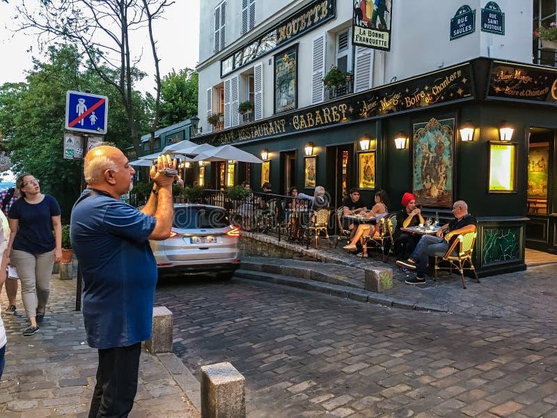 Den manliga turisten skjuter videoen utanför La Bonne Franquette, noterad kabaret på Montmartre i Paris, Frankrike royaltyfria bilder