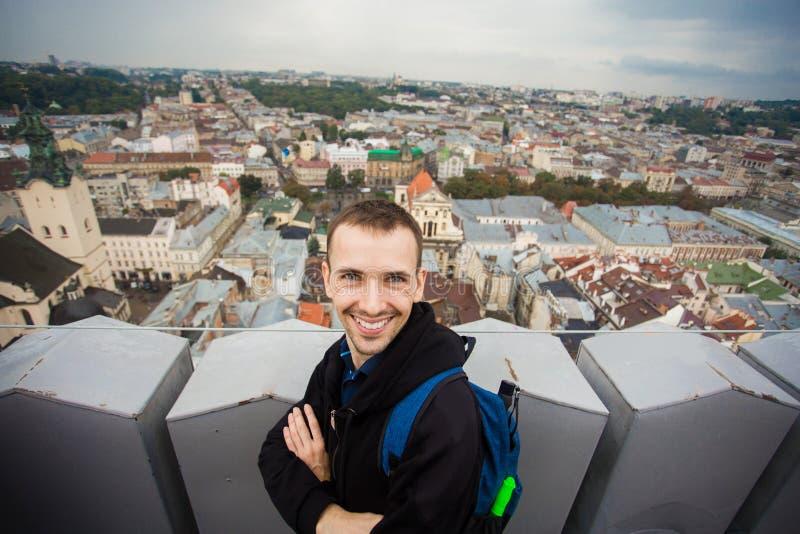 Den manliga turisten står överst av europeiskt stadshus med sikt av mitten av Lviv arkivfoton