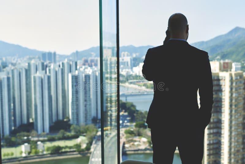 Den manliga vd:n är det stående near kontorsfönstret med sikt av högväxta skyskrapor arkivfoton