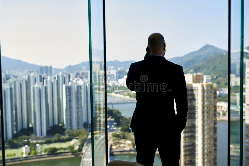 Den manliga vd:n är det stående near kontorsfönstret med sikt på en bakgrund för affärsmitt med kopieringsutrymme royaltyfria bilder