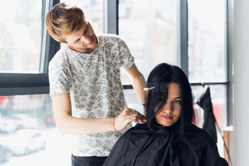 Den manliga yrkesmässiga frisören rätar ut hår för brunettkvinna` s genom att använda en hairstraightener i hårsalong arkivfoton